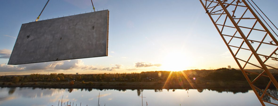 Picture of concrete wall hanging from crane while the sun sets over a lake in the background.
